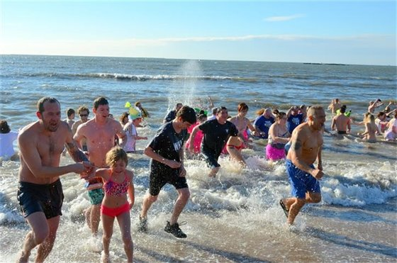 Over 200 brave frigid water, waves to aid breast cancer fight