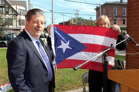 Mayor Rossi presents the Puerto Rican flag